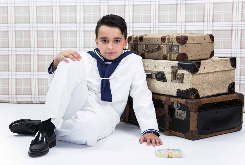Sesión fotos de Comunión en estudio niño con maletas