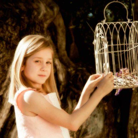 Sesión de fotografía comunión exteriores niña con jaula vintage