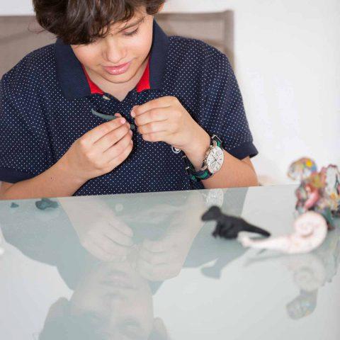 Niño en sesión de fotos construyendo con plastilina