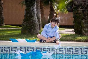 Foto exterior para comunión niño con barcos de papel