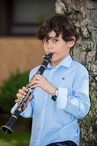 Niño con clarinete en sesión de fotos exterior